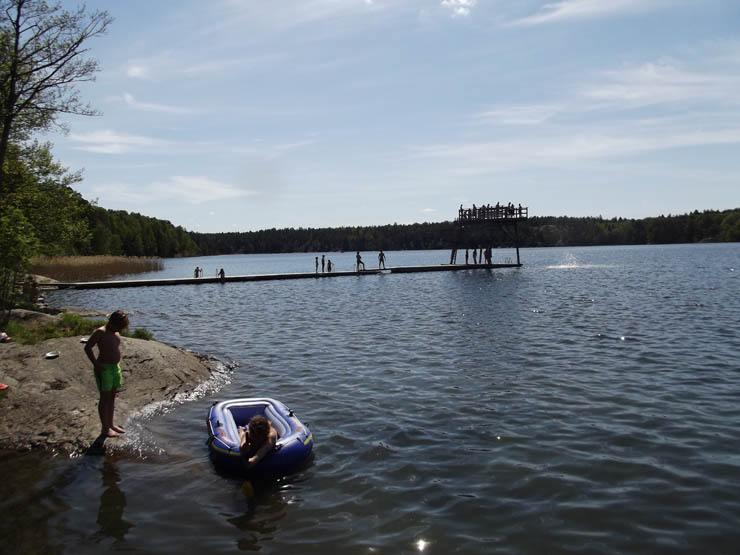 Flatenbadets Hopptorn & några barn med uppblåsbar båt<