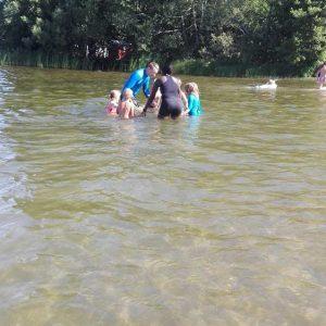 Samling i vattnet, vi står i ring och håller varandra i handen. Varje barn får säga sitt namn och, om det vill, doppa sig.
