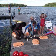 Glada och stolta barn får klänga på simlärarna. De får också jordgubbar, simmärken och diplom.