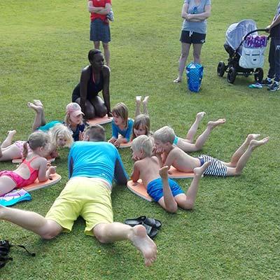 Barnen tränar torrsim - bröstsimmets bentag.